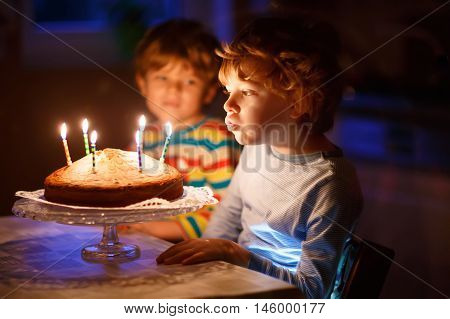 Adorable little kid boy celebrating his birthday and blowing candles on homemade baked cake, indoor. Brother on background. Birthday party for children.
