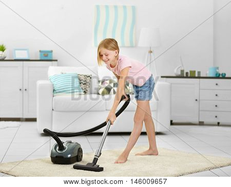 Little girl vacuuming floor with hoover