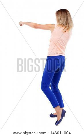 back view of standing girl pulling a rope from the top or cling to something. Isolated over white background. The blonde in a pink t-shirt has a hand.