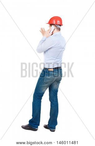 Backview of business man in construction helmet stands and enjoys tablet or using a mobile phone. businessman in a white shirt and a construction helmet talking on the phone and gesticulates.