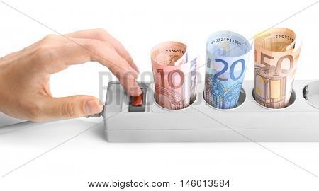 Woman hand turning off power socket with euro banknotes on white background