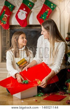 Happy young mother and daughter wrapping Christmas presents and looking at each other