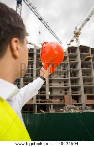View from back on construction engineer pointing at building site with red hardhat