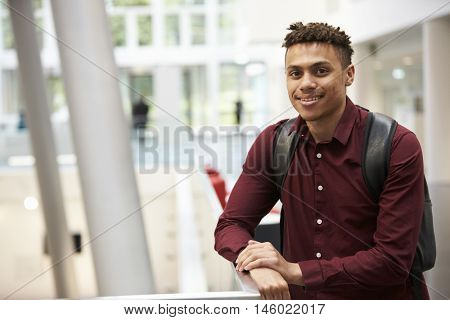 Young adult male student in modern university lobby