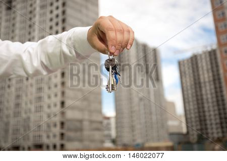 Young businessman holding keys from new real estate at building site