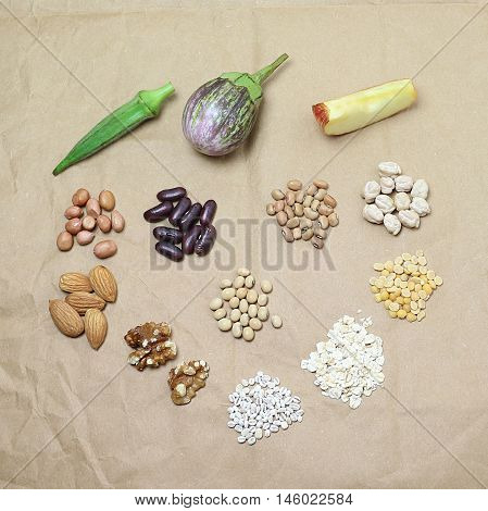 Vegetarian food that is said to fight cholesterol, including okra, eggplant, apple, and chickpea.
