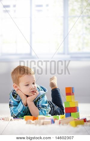 Adorable gingerish little boy laying on floor, playing with building cubes.?
