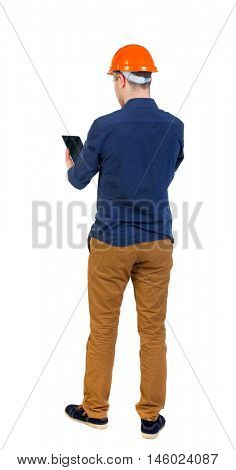 Backview of business man in construction helmet stands and enjoys tablet or using a mobile phone. man in a blue shirt and a helmet stands with his back holding hands plashnet.
