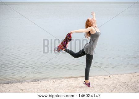 The red-haired woman in a flying pose on the beach