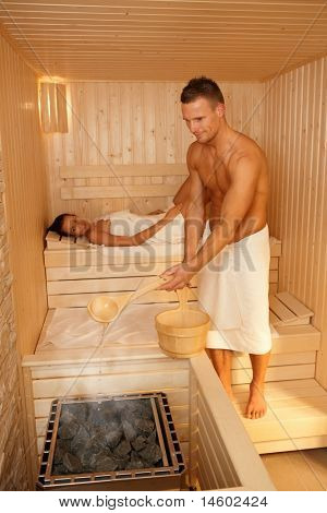 Couple using sauna, man making steam, smiling, woman lying in background.?
