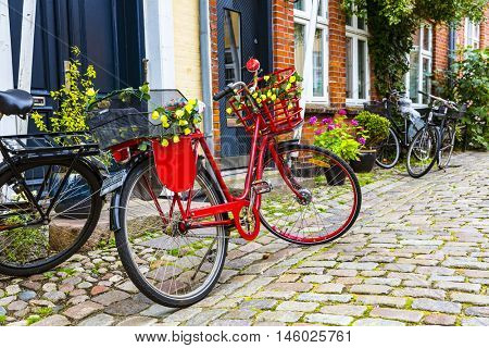 Retro vintage red bicycle on cobblestone street in the old town. Ribbe, Denmark