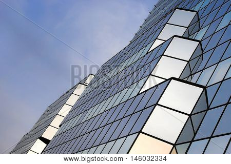 The glass walls of tall buildings in the background of the cloudy sky