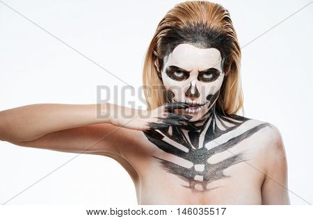 Portrait of young woman with gothic skeleton makeup over white background
