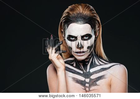 Portrait of young woman with scared halloween makeup over black background