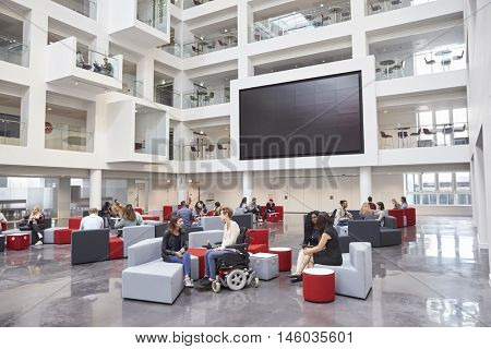 Students socialising under AV screen in atrium at university