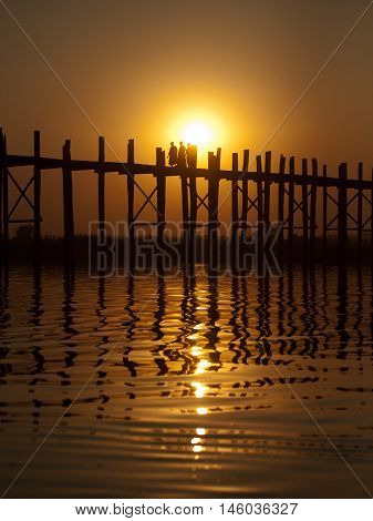 U Bein Bridge at sunset with people crossing Ayeyarwady River Mandalay Myanmar