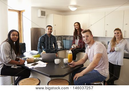 Portrait Of Students Relaxing In Kitchen Of Accommodation