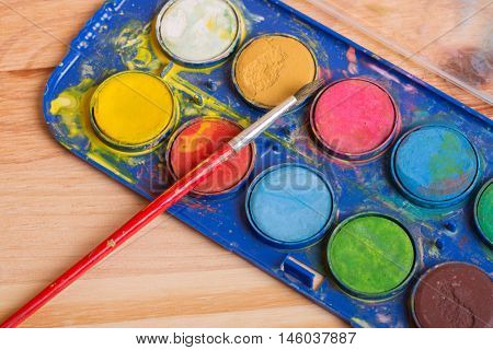 Dirty brushes with paint on a wooden background