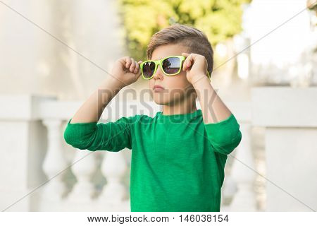 Stylish Little Boy Holding Sunglasses . Portrait Of A Child . Stylish Boy .