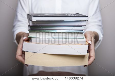 Reading and student college concept. Woman holding a pile of old books. Female librarian hands.