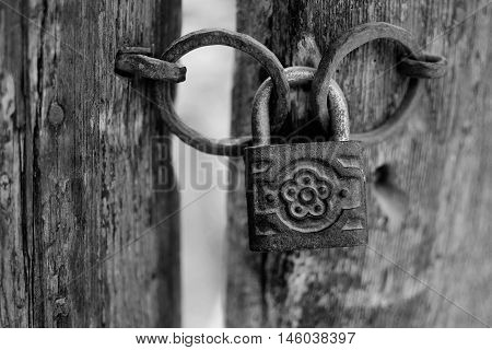Old Rusty Decorated Padlock On A Wooden Door In B&w. Vintage Corroded Padlock On A Ancient Gate Back