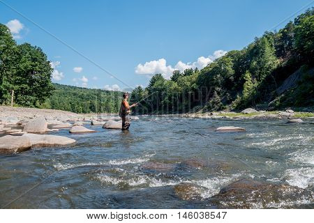 a fisherman wearing waders casts his lure into a river