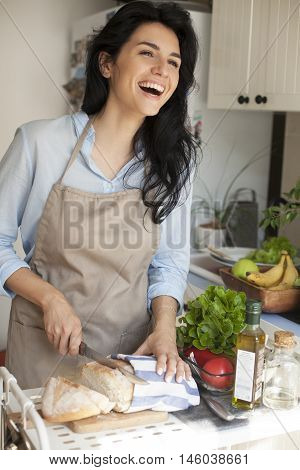 Beautiful woman in Kitchen smiling and cooking