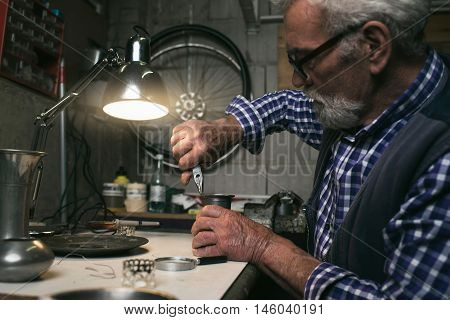 Man fixing an antique vase with pincers