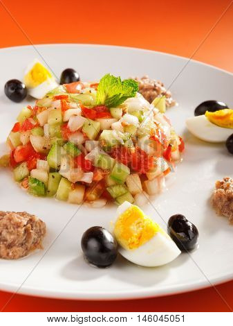 Tunisian salad with cucumbers tuna fish eggs and olives. Vertical shot