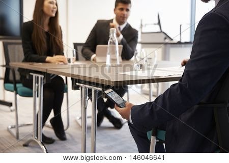 Businessman Discreetly Receiving Text Message During Meeting