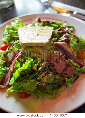 Green salad with duck magret and foie gras in french restaurant