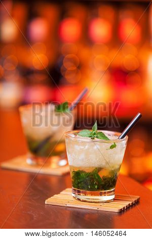 Two Mint Julep cocktails shot on a bar counter in a nightclub