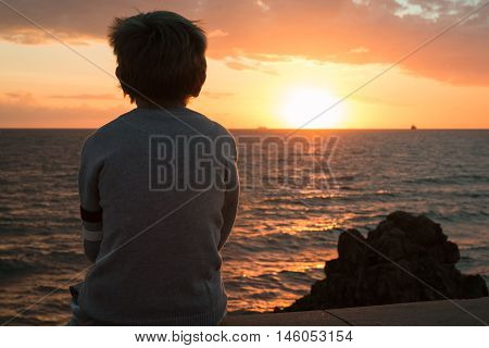 Silhouette of a Child in Front of Sea at Sunset