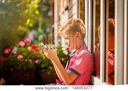 Little boy child kid playing games on smartphone mobile phone outdoor.