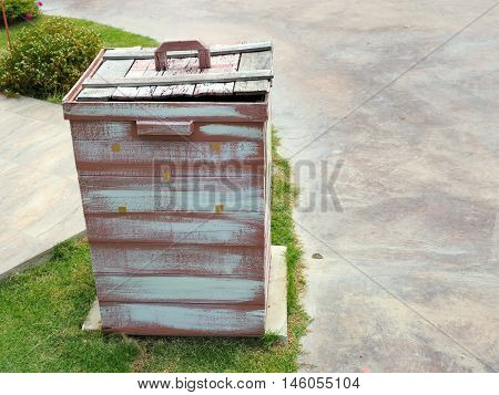 Wooden slatted litter bin beside the side walk
