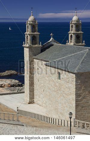 Spain Galicia Muxia Virxen de la Barca Sanctuary on Atlantic coast sail boat at sea
