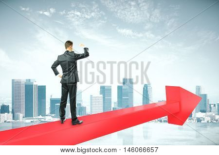 Success concept with businessperson standing on red chart arrow and looking intor the distance on citybackground