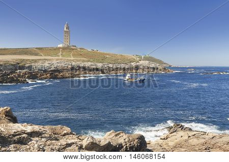 Spain Galicia A Coruna Hercules Tower Lighthouse in daylight clear sky rocky coastline Atlantic Ocean waters a boat