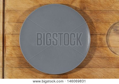 Flat grey ceramic plate on wooden cutting board directly from above