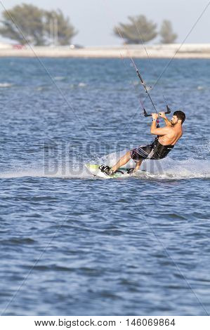 Tampa Bay Florida USA - February 28 2011: Kiteboarder glides across small chop off Fort De Soto