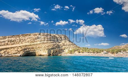 Matala beach on Crete island, Greece. Tourists relax and bath in crystal clear water of Matala in south of Creta. There are many caves near the beach. poster