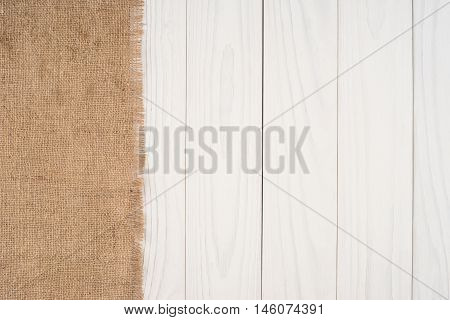 The texture of burlap on white background wooden table. Top view.