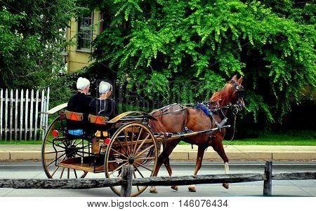 Intercourse Pennsylvania- June 4 2015: Two Amish women with white caps riding in an open horse buggy on Queen Road *