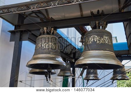 Bells with a beautiful ornament. Bells hung on a metal beam. Theodosius Pechersky Church (belongs to the Ukrainian Orthodox Church) built late XVII century