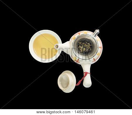 Closeup beautiful ceramic tea pot with dried tea leaves on tea strainer and brown tea in a cup of tea isolated on black background in top view with clipping path