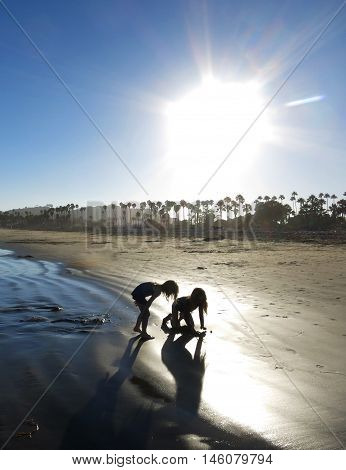 Two young girls playing in the sand on the beach