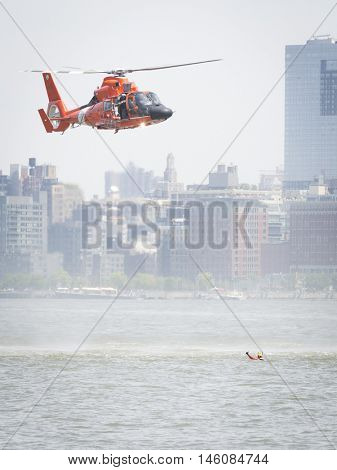 JERSEY CITY NJ MAY 29 2016: The orange U.S. Coast Guard MH-65 Dolphin helicopter crew and rescue swimmer perform a Search and Rescue demonstration at Liberty State Park during Fleet Week 2016.