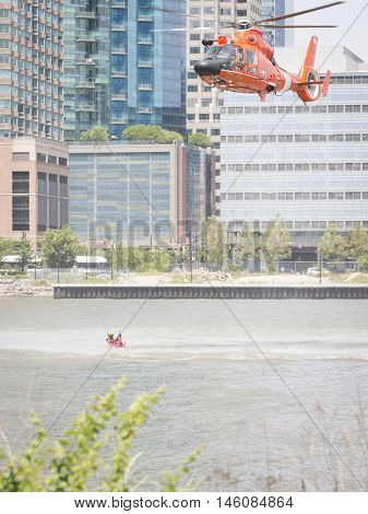 JERSEY CITY NJ MAY 29 2016: The orange U.S. Coast Guard MH-65 Dolphin helicopter and crew performing a Search and Rescue demonstration at Liberty State Park during Fleet Week 2016.
