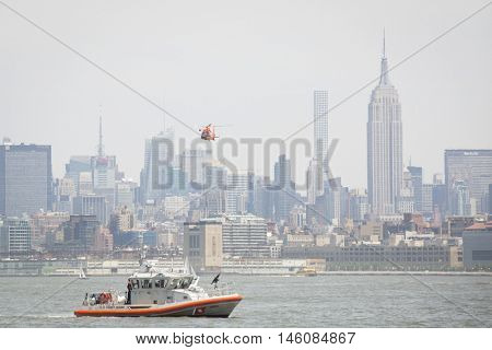 JERSEY CITY NJ MAY 29 2016: The orange U.S. Coast Guard patrol boat and MH-65 Dolphin helicopter performing a Search and Rescue demonstration at Liberty State Park during Fleet Week 2016.