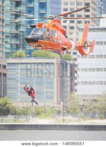 JERSEY CITY NJ MAY 29 2016: U.S. Coast Guard rescue swimmer waves when hoisted by line into a USCG MH-65 Dolphin helicopter hovering above during a Search and Rescue demonstration for Fleet Week 2016.